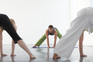 Yoga teacher at front of class demonstrating prasarita padottanasana